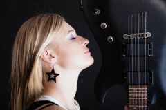 Rock music. Girl musician guitarist with electric. Rock music. Blonde girl guitarist musician performer with electric guitar musical string instrument on black Stock Photography