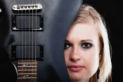 Rock music. Girl musician guitarist with electric. Rock music. Blonde girl guitarist musician performer hiding behind electric guitar musical string instrument Royalty Free Stock Image