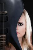 Rock music. Girl musician guitarist with electric guitar. Rock music. Blonde girl guitarist musician performer hiding behind electric guitar musical string Stock Photography