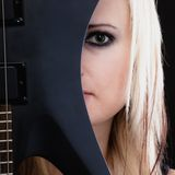 Rock music. Girl musician guitarist with electric guitar. Rock music. Blonde girl guitarist musician performer hiding behind electric guitar musical string Stock Image
