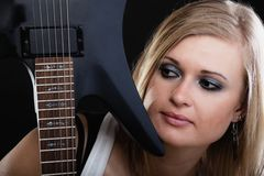 Rock music. Girl musician guitarist with electric guitar. Rock music. Blonde girl guitarist musician performer hiding behind electric guitar musical string Royalty Free Stock Image