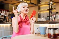 Joyful senior woman smiling to you. Rock music. Joyful senior woman smiling to you while listening to rock music royalty free stock photography