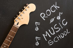 Rock music school. With electric guitar on blackboard background Stock Photo