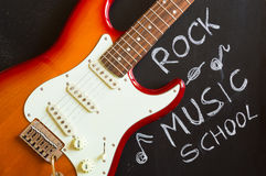 Rock music school. With red electric guitar on blackboard background Royalty Free Stock Image
