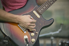 Rock Music Sound. Detail of a Guitarist who plays his electric guitar at a live rock music concert Stock Photos