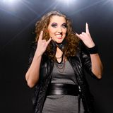 Rock music woman. Funny rock and roll woman is showing the sign of the horns Stock Photo