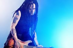 Rock musician. Heavy metal musician  is playing electrical guitar. Shot in a studio Stock Photo