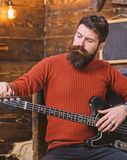 Rock musician with brutal look posing with instrument. Bearded man tuning electric guitar. Man with stylish beard and stock images