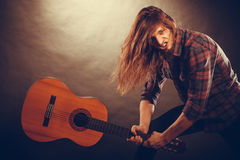 Rock musician destroys his guitar. Rock music energy people feelings concept. Mad rock guitarist destroys his guitar Stock Photography