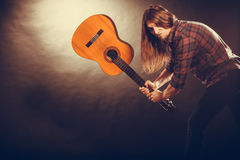 Rock musician destroys his guitar. Rock music energy people feelings concept. Mad rock guitarist destroys his guitar Royalty Free Stock Photo