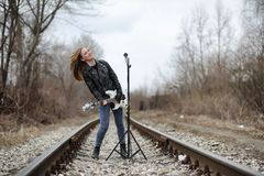 A rock musician girl in a leather jacket with a guitar. A rock musician girl in a leather jacket with guitar Stock Images