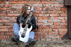 A rock musician girl in a leather jacket with a guitar. A rock musician girl in a leather jacket with guitar Royalty Free Stock Photo