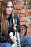 A rock musician girl in a leather jacket with a guitar. A rock musician girl in a leather jacket with guitar Royalty Free Stock Photos