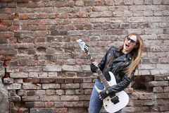 A rock musician girl in a leather jacket with a guitar. A rock musician girl in a leather jacket with guitar Stock Photo