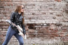 A rock musician girl in a leather jacket with a guitar. A rock musician girl in a leather jacket with guitar Royalty Free Stock Image