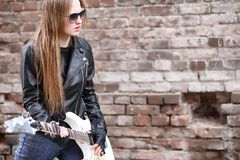 A rock musician girl in a leather jacket with a guitar. A rock musician girl in a leather jacket with guitar Stock Image