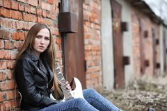 A rock musician girl in a leather jacket with a guitar royalty free stock photography