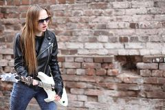 A rock musician girl in a leather jacket with a guitar Stock Image