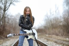 A rock musician girl in a leather jacket with a guitar. A rock musician girl in a leather jacket with guitar Stock Photography