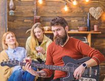 Rock musician with long beard and tattooed arm playing guitar. Bearded man with stern eyes looking at camera. Guitarist royalty free stock image