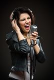 Rock musician with mic and earphones Royalty Free Stock Photography
