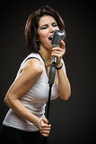 Rock musician with microphone. Half-length portrait of female rock musician with microphone. Concept of rock music and rave royalty free stock images