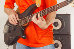 Rock musician playing the electric bass guitar Stock Images