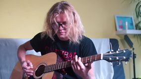 Rock musician plays acoustic guitar at home. Hairy rock musician with glasses. Sitting on the couch. Plays an acoustic guitar at home stock footage