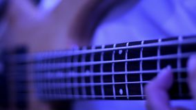 Rock musician plays solo bass guitar. Close - up bass guitar solo. Close-up of rock guitarist hands. Bass guitarist. Rock musician is playing a solo on the bass stock video footage