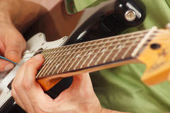 Rock musician put fingers for chords on electric guitar close up Royalty Free Stock Photos