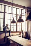 Rock musician sitting near window and composing new song. Sitting and composing. Rock musician with hair bun sitting near window and composing new song royalty free stock photos