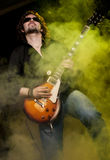 Rock'n'roll. A man playing eletctric guitar on a stage Stock Images