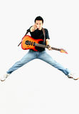 Rock'n roll. Young guy jumping with guitar Royalty Free Stock Image