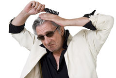 Rock'n'Roll attitude. Mature outdated man doing his hair Stock Photo