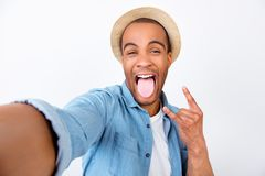 Rock n roll babe! Attractive young mulatto mixed raced guy is po. Sing on the camera, so playful. In casual wear, on pure white background, showing rock sign Royalty Free Stock Images