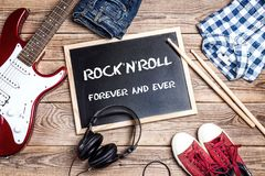 Rock`n`Roll background with blackboard, music equipment, clothes. And footwear on wooden table. Rock`n`Roll forever and ever Royalty Free Stock Photography