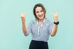 Rock n roll. Funny business lady looking at camera with rock sin. G. Studio shot, on light blue background Royalty Free Stock Photo