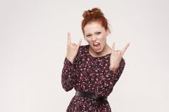 Rock n roll. Funny redhead lady looking at camera with rock sing royalty free stock images