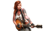 Rock'n Roll girl with tattoo. Portrait of young attractive girl with lots of tattoo playing electric guitar taken against color background Stock Photography