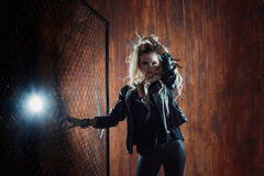 Rock`n`roll girl, young beautiful woman dances in dark alley, against the fence mesh Stock Images