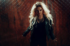 Rock`n`roll girl, young beautiful woman dances in dark alley, against the fence mesh Stock Photos