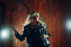 Rock`n`roll girl, young beautiful woman dances in dark alley, against the fence mesh Royalty Free Stock Images