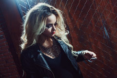 Rock`n`roll girl, young beautiful woman dances in dark alley, against the fence mesh stock image