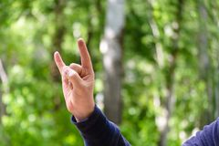 Rock `n roll hand sign. Gesture mens hand of three fingers. Concept of positive, Rock and Roll, win, devil horns. Closeup view on stock image