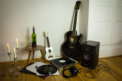 Rock'n'roll setup with ukulele, acoustic guitar, speaker, candle Royalty Free Stock Photography