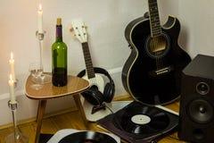 Rock'n'roll setup with ukulele, acoustic guitar, speaker, candle Royalty Free Stock Image