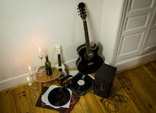 Rock'n'roll setup with ukulele, acoustic guitar, speaker, candle Stock Photos