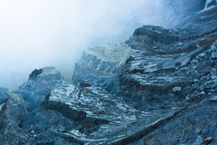 Rock near ijen crater covers by heavy smoke. From the crater royalty free stock image