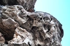 Rock with numerous holes similar to the eye socket. Against the blue sky Royalty Free Stock Image