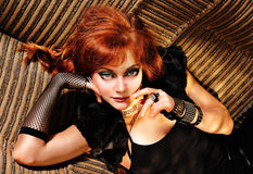 Rock Nymph. Beautiful red-haired girl wearing black rock style clothes and lying on a couch Stock Photos